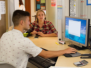 Financial Aid technician helping a student at the window