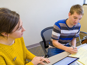 A student getting help from a tutor at the writing center